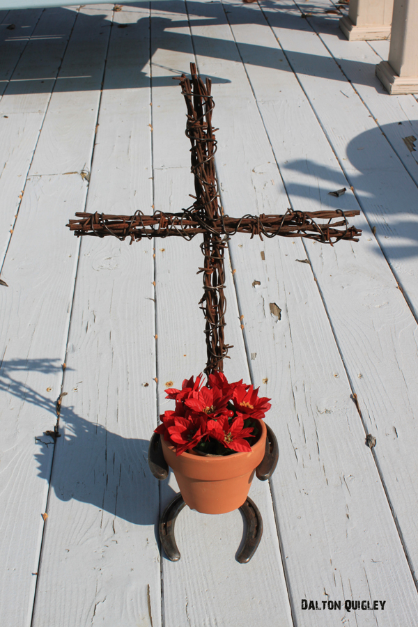 "Image of a Cross made of Barbed Wire holding a 4"" pot with flower."